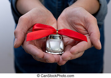 Woman's hands holding toy car with ribbon on it. New car gift concept
