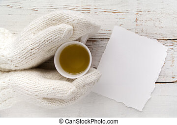 Woman's hands in gloves holding a cup of tea with blank card on white wooden table