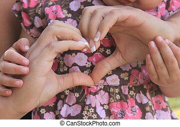woman's hands in shape of heart