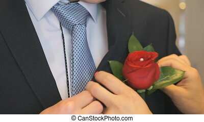Woman's hands insert boutonniere in pocket - Close-up of...