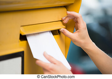 Woman's Hands Inserting Letter In Mailbox - Closeup of...