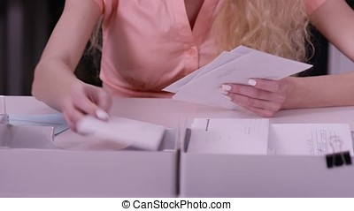 Woman's hands iterate over the letters in envelopes. Close...