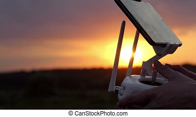 Woman's hands keep a control panel to operate a drone at sunset