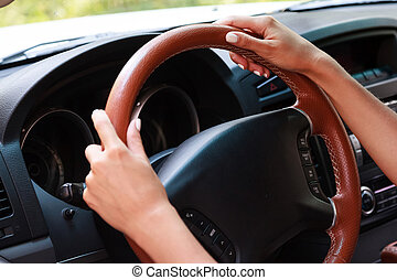 Woman's hands on a steering wheel of a car
