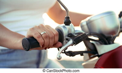 Woman's hands on steering wheel, girl driving moped or...