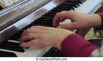 Woman's hands on the keyboard of the piano