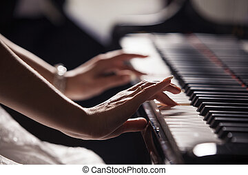 Woman's hands on the piano keyboard