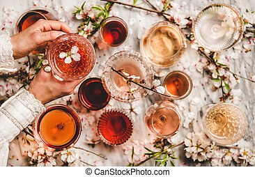 Womans hands over dofferent shades of rose wine in glasses and spring blossom flowers over white background, top view. Wine shop, bar, wine tasting, wine list concept
