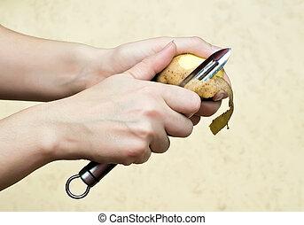 hands peeling potato - womans hands peeling potato with ...