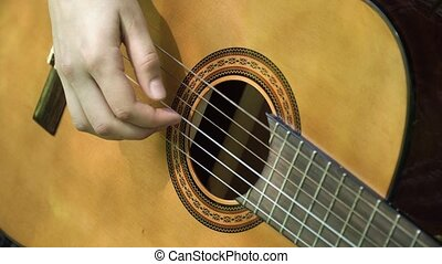 Woman's hands playing acoustic guitar. - Female hand playing...
