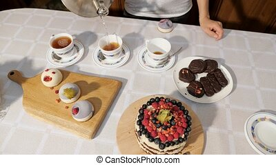 Woman's hands pour tea in cups at home on the table with sweets to celebrate birthday.