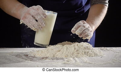 woman's hands pour the milk to dough for kneading on the ...