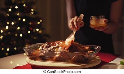 Woman's hands pouring honey and mustard on roasted goose....