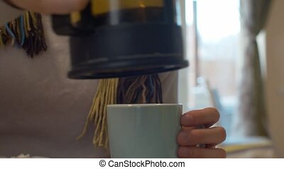 Woman's hands pouring tea into the cup