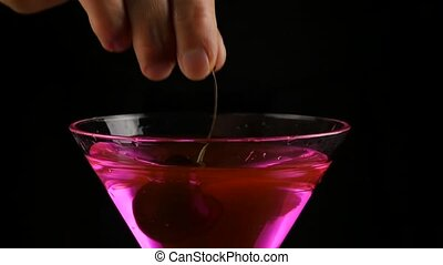 woman's hands prepares a pink alcohol cocktail with cherry...