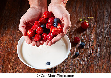 Womans hands preparing healthy natural breakfast fron ripe berries and organic milk in a bowl on a wooden table.