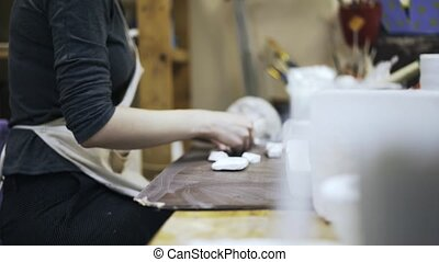 Womans hands putting pieces of gypsum, side view - Side view...