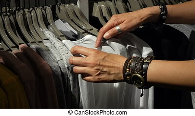 Woman's hands run across a rack of clothes
