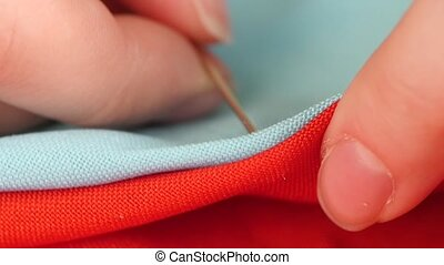 Woman`s hands sewing with needle, white thread and thimble on red and blue clothes, close up, slow motion