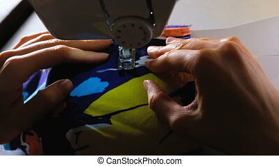 Womans hands sews on the sewing machine, paving the line,...
