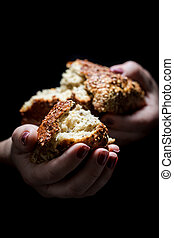 Woman's hands sharing a loaf of bread