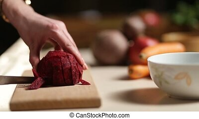 Woman's hands slicing beet on wooden cutting board