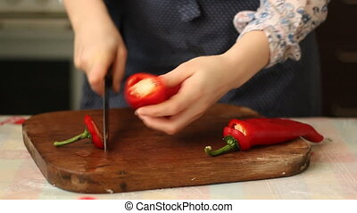 Woman's hands slicing sweet Red Bell Pepper on a wooden cutting board