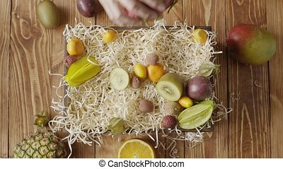 Woman's hands take out healthy exotic tropical fruits from...