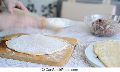 Woman's hands unroll a dough for pelmeni - Woman's hands...