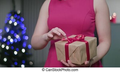 Woman's Hands Unwrapping a Christmas Gift