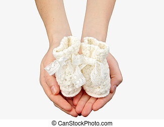 woman's hands with baby's bootee