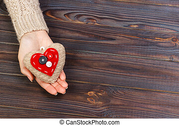 Woman's hands with beautiful accurate knitted red heart. White cozy knitted sweater on wooden background. Concept of giving help. Love concept with copyspace