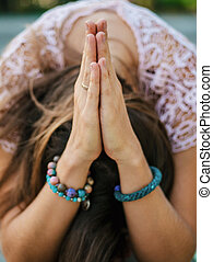 Woman's hands with bracelets together symbolizing prayer and...