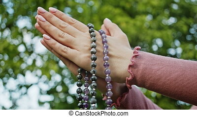 Woman's hands with mala beads or rosary together symbolizing prayer and gratitude. Mudra. Yoga concept. Concentrated girl standing with hands in namaste and meditating or praying