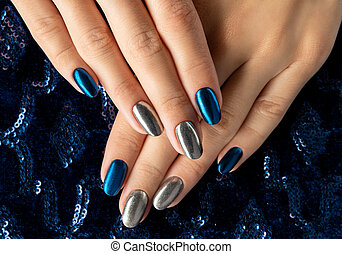 Womans hands with manicure on the creative blue sparkle background