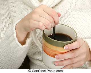 Woman's Hands with Mug of Coffee and Spoon