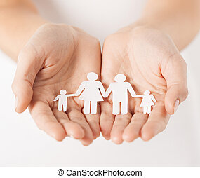 woman's hands with paper man family - close up of womans...