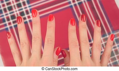 Woman's hands with red manicure appear on red background