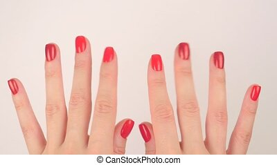 Woman's hands with red manicure appear on white background