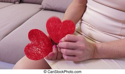 Woman's hands with two red paper hearts