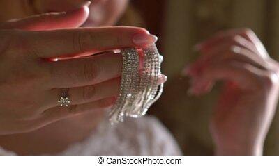 Woman's jewelry earrings waving slowmotion. Bride put on