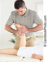 A woman's leg is massaged by a masseur in his surgery