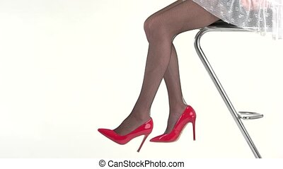 Woman's legs in high heels. Lady sitting on bar chair....