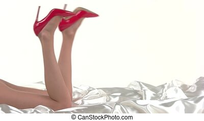 Woman's legs in red heels. Glossy female footwear. How to...