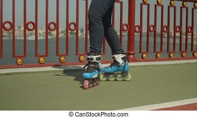 Woman's legs in roller skates riding outdoors - Close-up of...