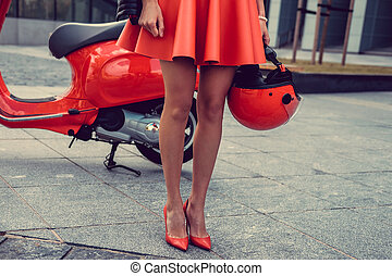 Woman's legs near red scooter.