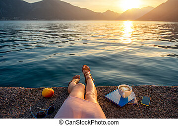 Woman's legs on the pier at sunset