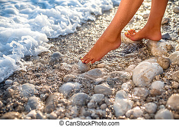Woman's legs on the stone beach with water
