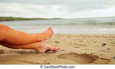 Womans legs sitting on the beach on a cloudy day