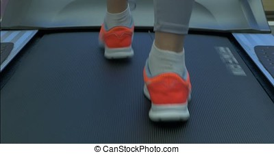 Woman's muscular legs on treadmill. woman's muscular legs on treadmill, closeup. girl's legs on treadmill or running machine close up